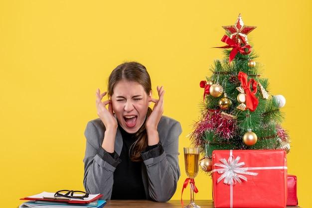 전면보기 그녀의 손가락 크리스마스 트리와 선물 칵테일로 귀를 덮고 책상에 앉아 소녀를 외쳤다
