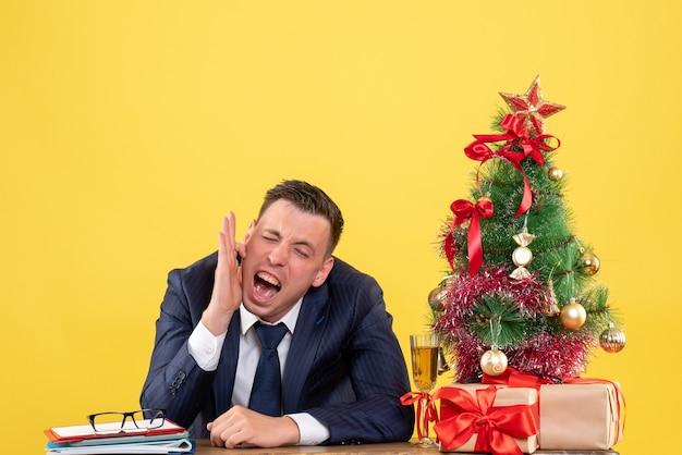 Vista frontale dell'uomo gridato che tiene il suo orecchio seduto al tavolo vicino all'albero di natale e regali su giallo.