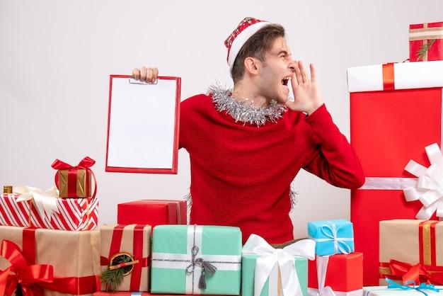 正面図は、クリスマスプレゼントの周りに座っているクリップボードをホッピングする若い男を叫んだ