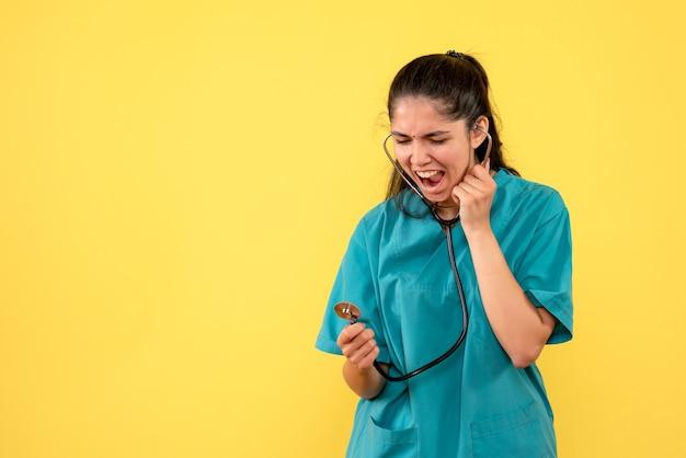 黄色の背景に立っている彼女の手で聴診器を保持している女性医師を叫んで正面図