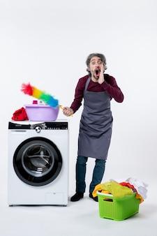 Vista frontale che grida l'uomo della governante che tiene lo spolverino in piedi vicino al cesto della biancheria della lavatrice sul muro bianco