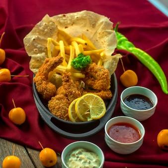 Вид спереди креветки в кляре с картофелем фри жареный лаваш и соусы