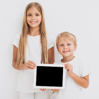 Front view siblings holding a tablet mock-up
