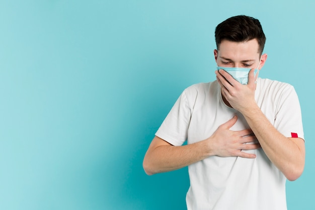 Front view of sick man coughing while wearing a medical mask