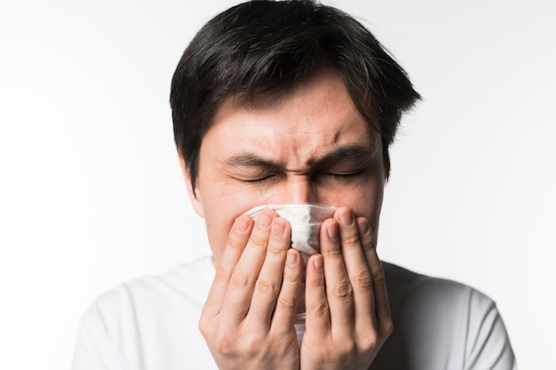 Front view of sick man sneezing into napkin