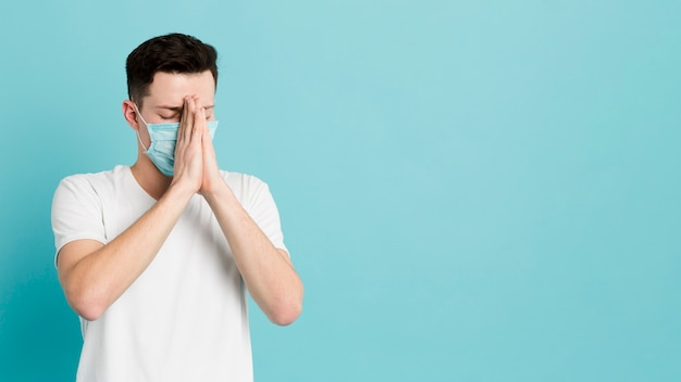 Front view of sick man with medical mask praying
