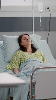 Front view of sick woman falling asleep recovering after cardiology recovery in hospital ward during medical therapy