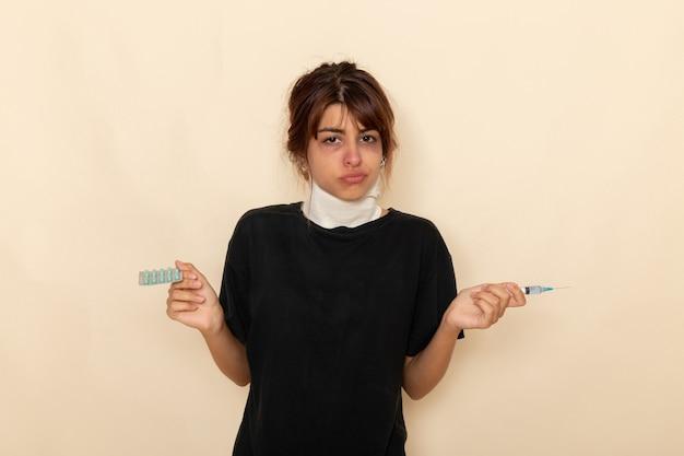 正面図病気の若い女性が気分が悪く、白い表面に注射と丸薬を保持している