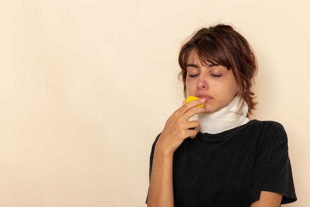 病気の若い女性が気分が悪く、白い表面にレモンを保持している正面図