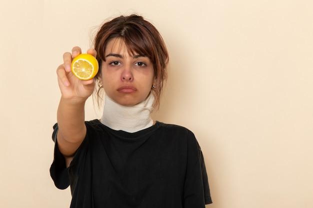 病気の若い女性が気分が悪く、白い机の上にレモンを保持している正面図