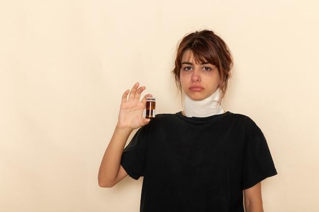 病気の若い女性が気分が悪く、白い表面に丸薬を保持している正面図