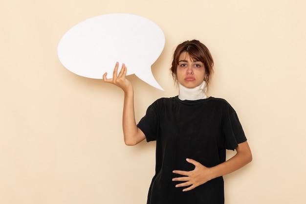 白い机の上に巨大な白い看板を持って気分が悪い正面図病気の若い女性