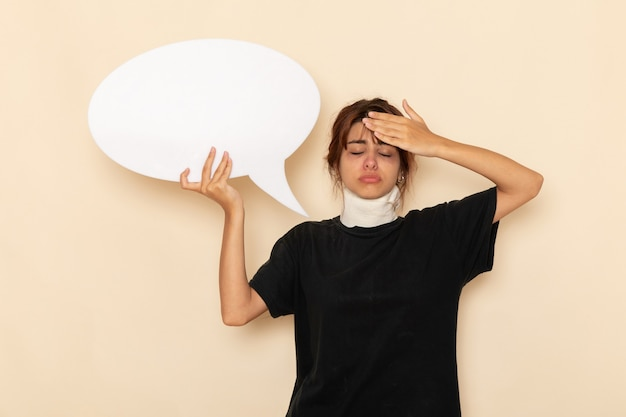 正面図病気の若い女性は白い表面に巨大な白い看板を持って気分が悪い