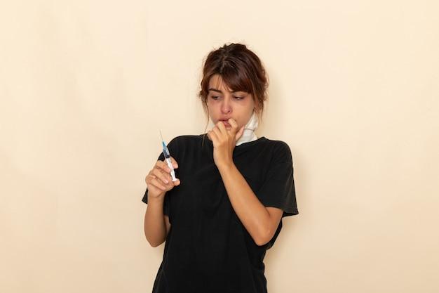 Vista frontale giovane donna malata sensazione di malessere e tenendo l'iniezione su una superficie bianca