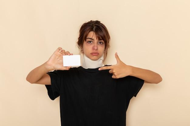 白い机の上に白いカードを持って気分が悪い正面図病気の若い女性
