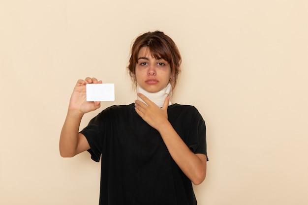 正面図病気の若い女性は、明るい白い表面に白いカードを持って気分が悪い
