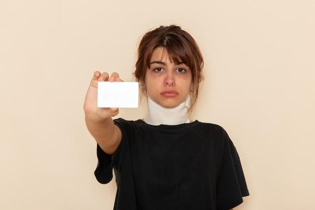 正面図病気の若い女性が白い表面に白いカードを持って気分が悪い