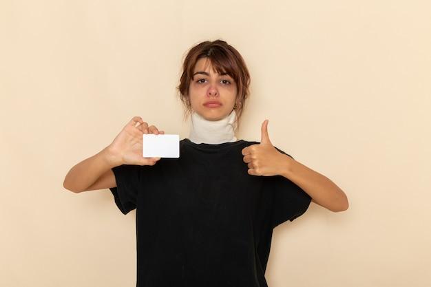 正面図病気の若い女性は、明るい白い表面に白いプラスチックカードを持って気分が悪い