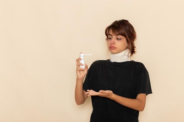 Giovane femmina malata di vista frontale che si sente male e che utilizza spray per la gola sulla superficie bianca chiara