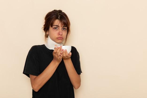正面図病気の若い女性は非常に気分が悪く、白い表面でハーブティーを飲む