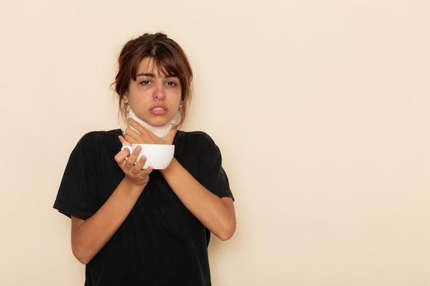 正面図病気の若い女性は非常に気分が悪いと明るい白い表面でハーブティーを飲む