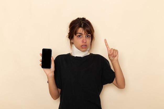Вид спереди больная молодая женщина чувствует себя очень плохо и держит телефон на белом столе