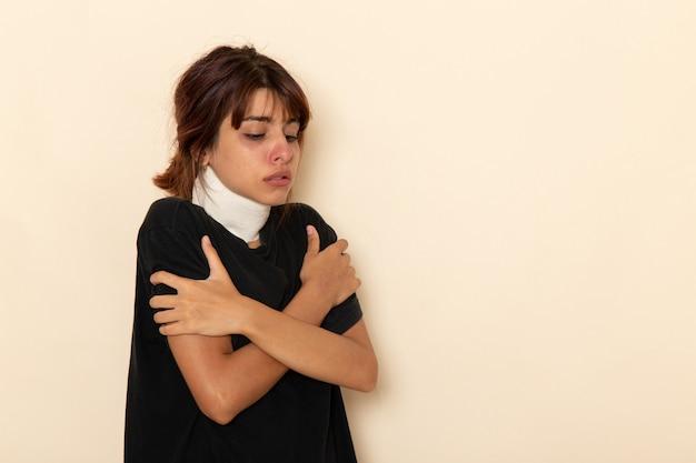 Вид спереди больной молодой женщины, чувствующей себя очень плохо и дрожащей от лихорадки на белой поверхности