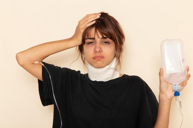 Вид спереди больной молодой женщины, чувствующей себя очень плохо и использующей пипетку на светлой белой поверхности