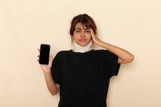 Giovane femmina malata di vista frontale che si sente molto male e che tiene il telefono avendo mal di testa sulla superficie bianca