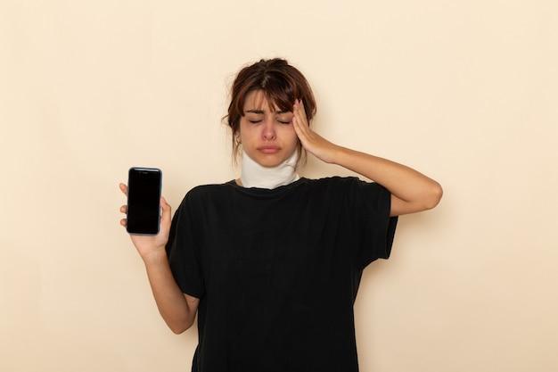 Giovane femmina malata di vista frontale che si sente molto male e che tiene il telefono sulla superficie bianca