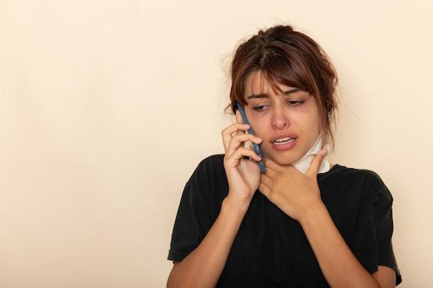Giovane femmina malata di vista frontale che si sente molto male e parla al telefono su una superficie bianca