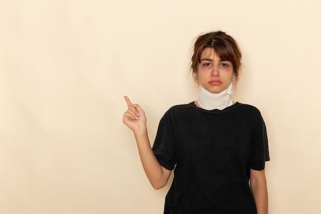 Вид спереди больной молодой женщины с высокой температурой и плохим самочувствием на белом столе