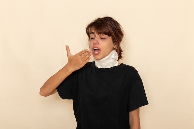 Вид спереди больной молодой женщины с высокой температурой и плохим самочувствием, чихающей на белой поверхности