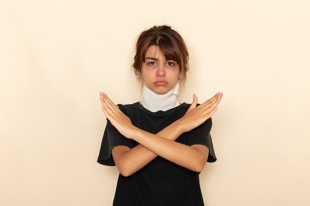 Giovane femmina malata di vista frontale con temperatura elevata e sensazione di malessere incrociando le braccia sulla superficie bianca