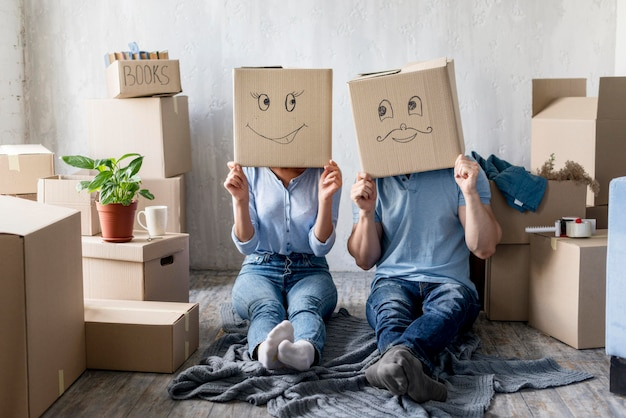 Front view of silly couple with boxes over heads at home on moving day