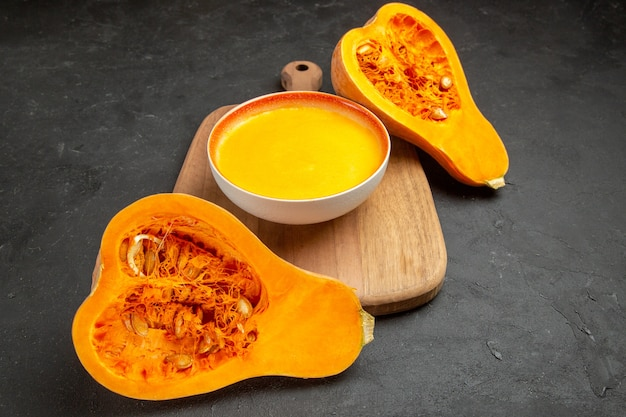 Vista frontale semplice zuppa di zucca con zucche fresche sulla tavola grigia cena liscia del ringraziamento