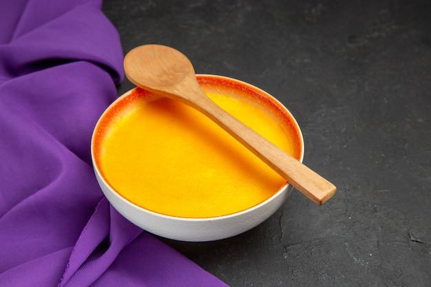 Вид спереди простой тыквенный суп с ложкой на сером столе