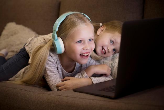 Vista frontale delle sorelle sul divano con un computer portatile
