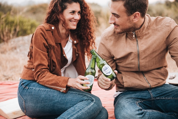 Front view sitting couple drinking beer