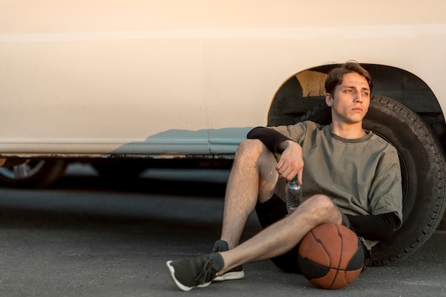 Front view sitting man with a basketball