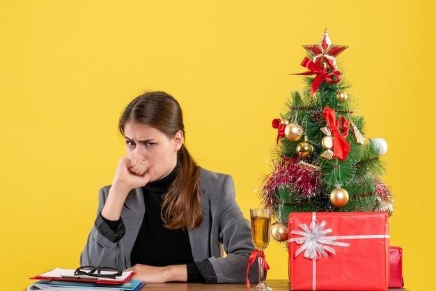 Ragazza scettica di vista frontale che si siede all'albero di natale dello scrittorio e cocktail dei regali