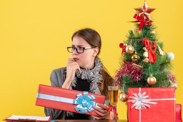 Ragazza scettica di vista frontale con gli occhiali che si siedono alla tavola che tiene il cocktail rosso dell'albero di natale e dei regali del giftbox