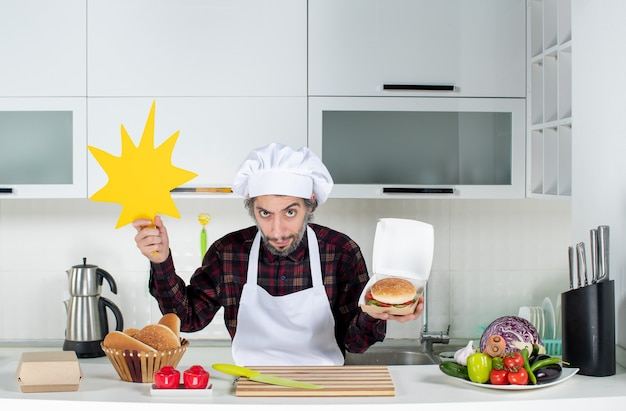 Front view of skeptical male chef holding up boom crunch sign and burger in modern kitchen