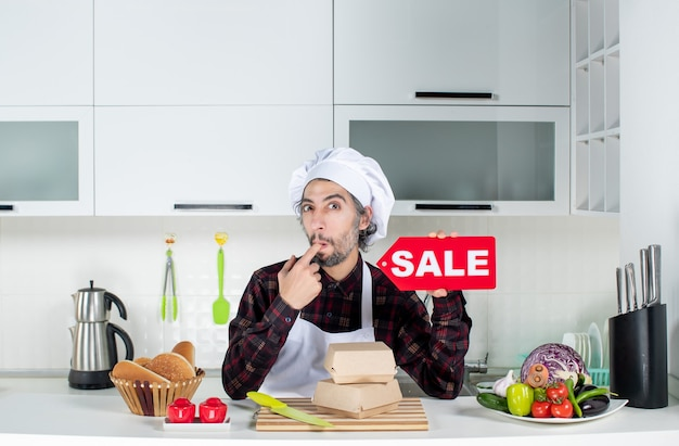 Front view of skeptical male chef in uniform holding up red sale sign putting finger in his mouth in modern kitchen