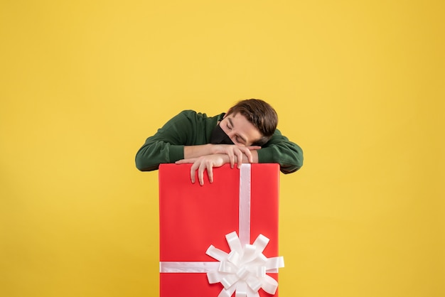 Vista frontale che dorme giovane uomo dietro grande confezione regalo su sfondo giallo spazio libero