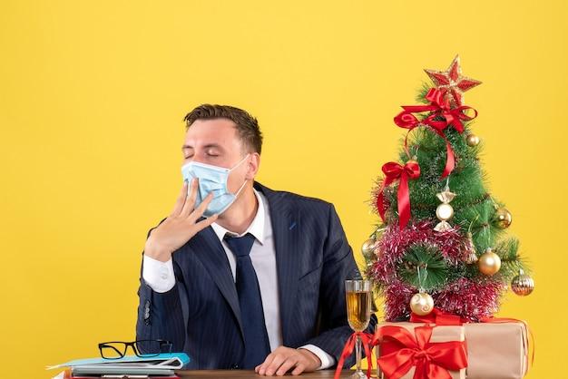 Vista frontale dell'uomo sonnolento di affari che si siede al tavolo vicino all'albero di natale e regali su giallo