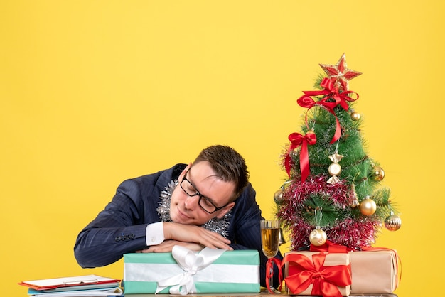 Front view of sleepy business man sitting at the table near xmas tree and presents on yellow