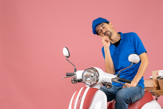 Front view of sleepy courier guy wearing hat sitting on scooter on pastel peach background
