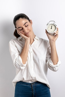 Front view of sleepy woman holding clock