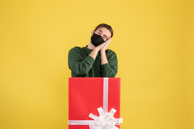 Вид спереди сонный молодой человек, стоящий за большой подарочной коробкой на желтом фоне